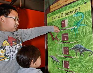 two children pointing to a dinosaur poster inside the Museum of Ancient Life
